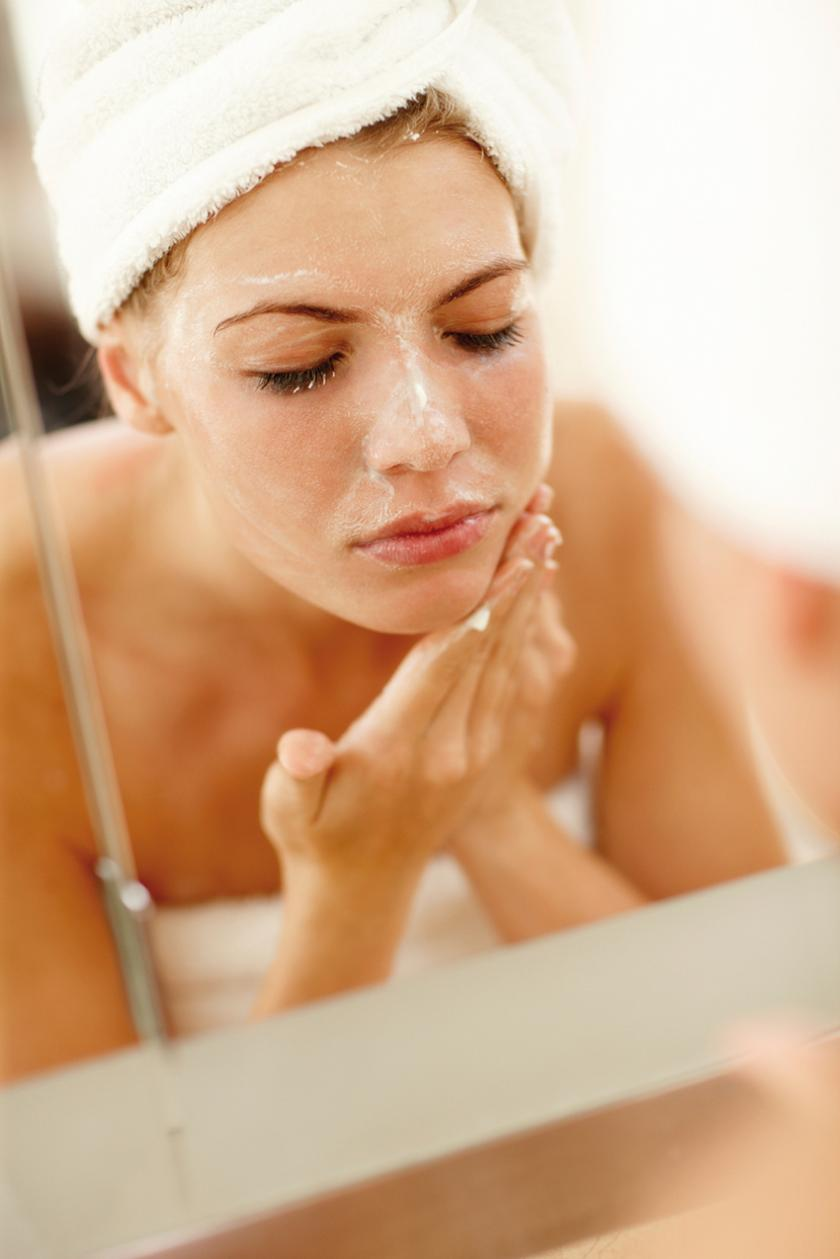 Woman washing face with scrub